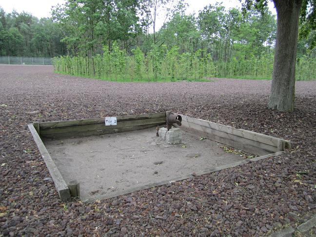 Fundament efter den inre lägerentrén. Träden i bakgrunden symboliserar fångbarackerna