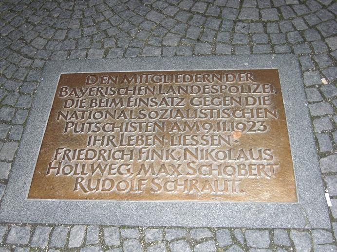 Minnestavla på marken för de fyra polismän som dödades under skottlossningen med nazisterna