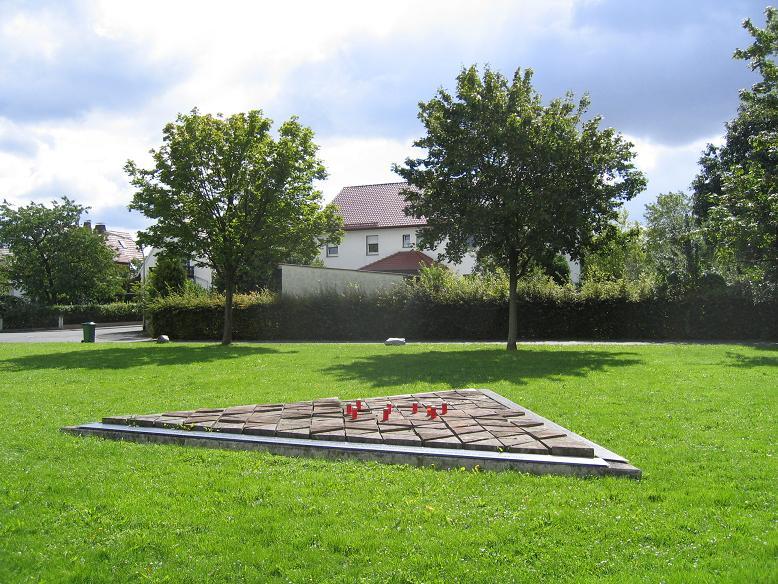 Minnesmonument på den f.d. uppsamlingsplatsen. Huset i bakgrunden är den f.d. lägerentrén
